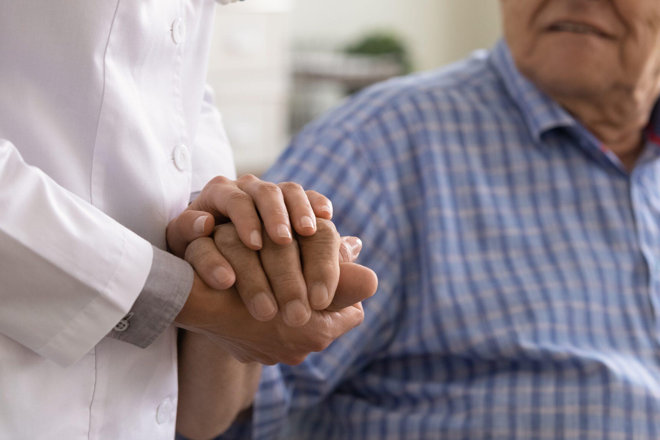 Close up caregiver holding mature man hand, psychological help