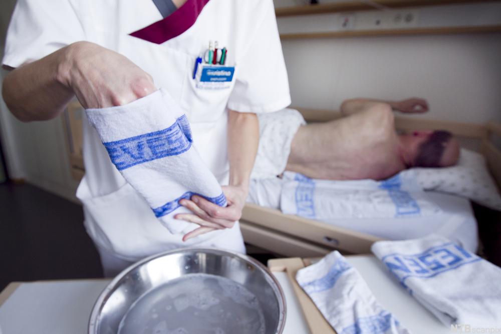 Helsefagarbeider skal vaske en mannlig pasient i en seng. Hun holder en klut.
