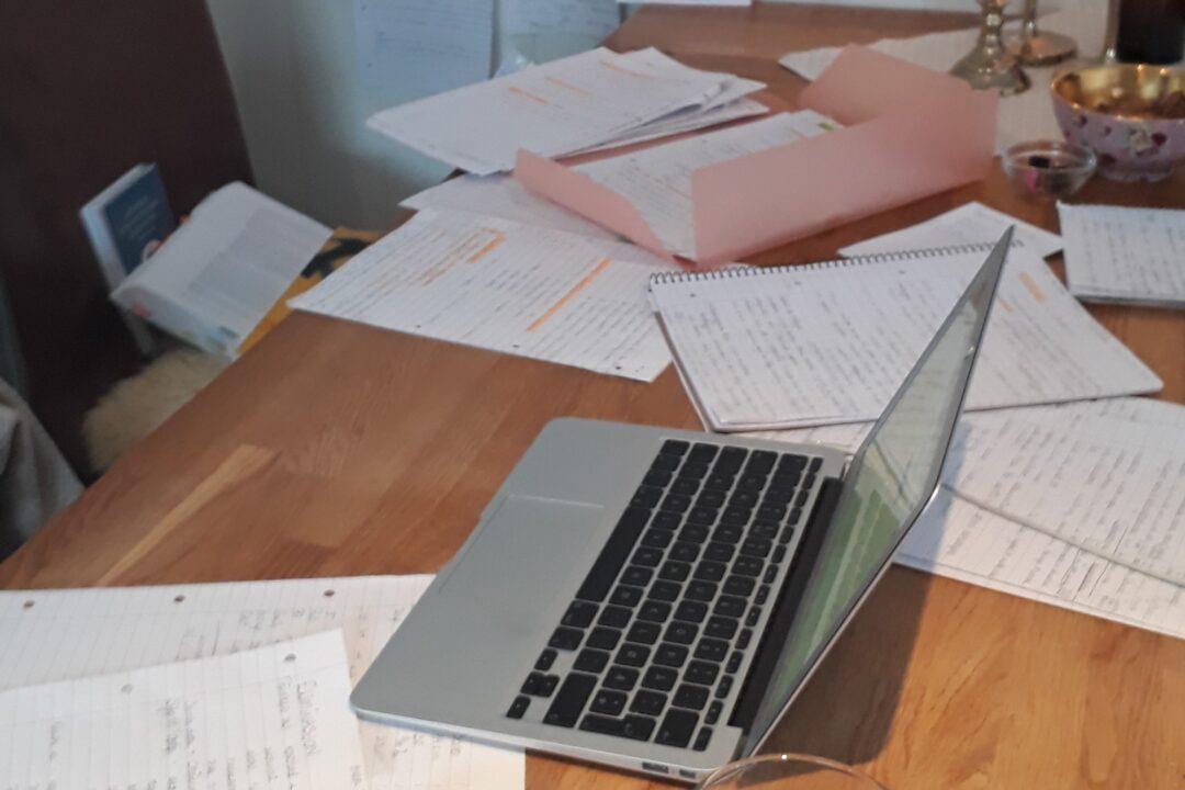 Bilde av bærbar pc og notater spredt utover bord